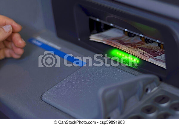 A bundle of paper money is inserted into the open ATM receiver - csp59891983