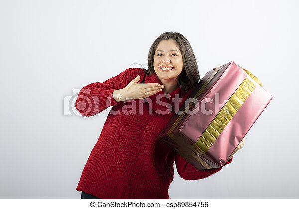 A young woman showing at a Christmas gift box - csp89854756