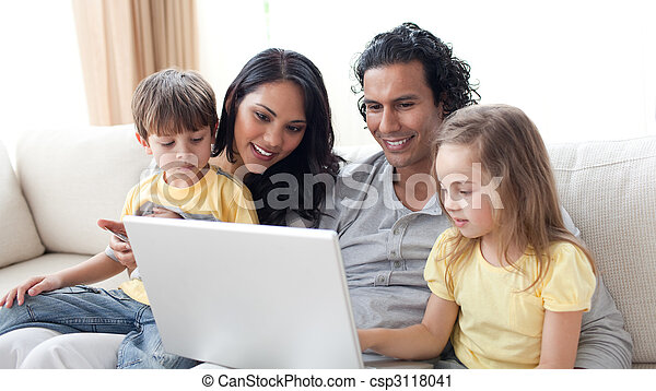 Affectionate parents using laptop with their children - csp3118041
