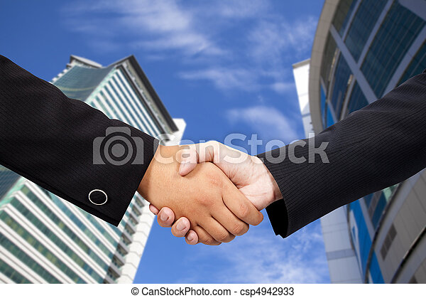 business people shaking hands against blue sky and modern building - csp4942933