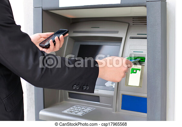 businessman inserts a credit card into the ATM to withdraw money and holding a phone - csp17965568