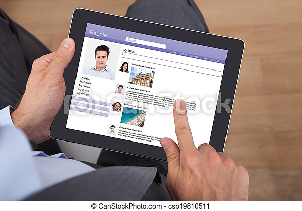 Businessman Surfing Social Networking Site On Digital Tablet - csp19810511