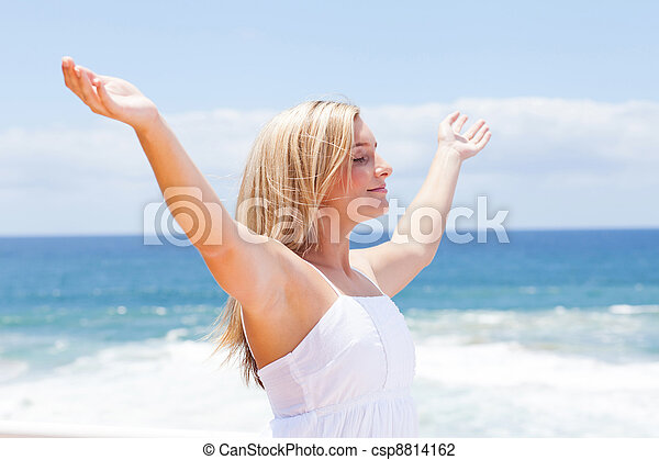 carefree young woman with arms open on beach - csp8814162