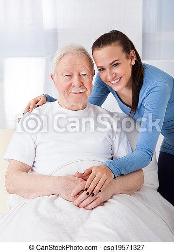 Caretaker With Senior Man At Nursing Home - csp19571327