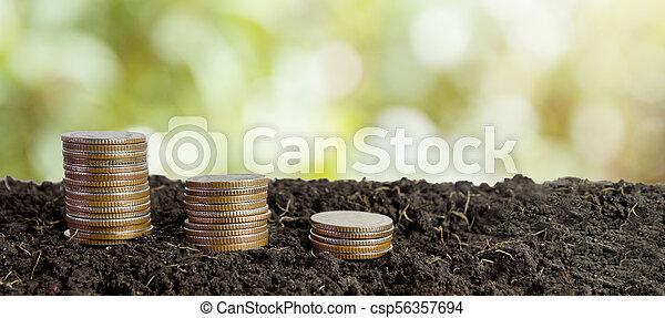 coins in soil, saving money concept - csp56357694