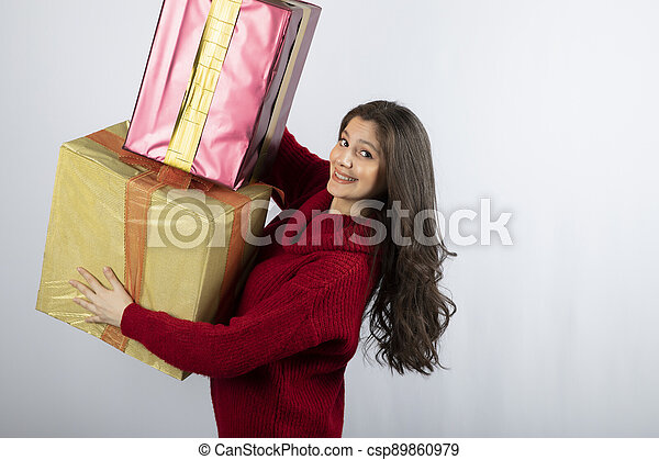 Cute woman in red sweater holding Christmas presents - csp89860979