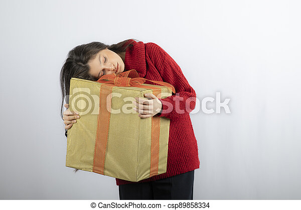 Cute woman in red sweater holding Christmas present - csp89858334