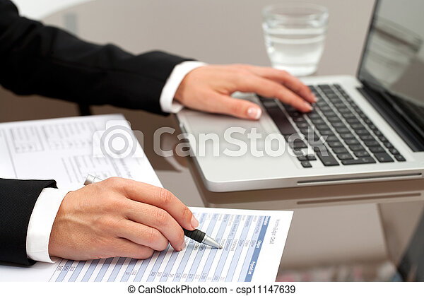 Female hands reviewing documents. - csp11147639