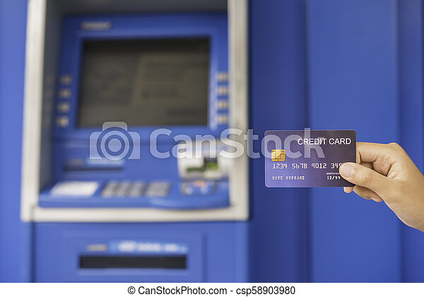 Hand inserting with a credit card into bank machine . Man using an atm machine with credit card to withdraw money - csp58903980