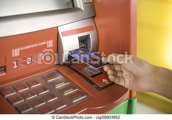 Hand inserting with a credit card into bank machine . Man using an atm machine with credit card to withdraw money - csp58903952