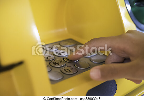 Hand inserting with a credit card into bank machine . Man using an atm machine with credit card to withdraw money - csp58903948