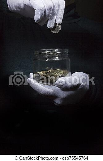 Hand throws a coin in a jar - csp75545764