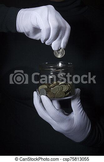 Hand throws a coin in a jar - csp75813055