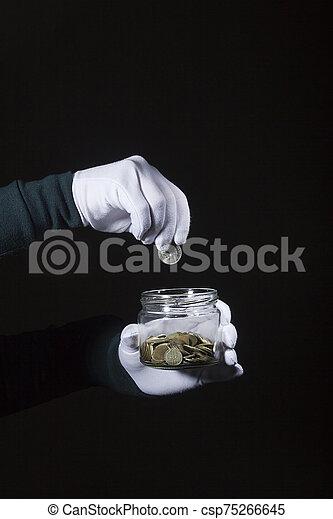 Hand throws a coin in a jar - csp75266645