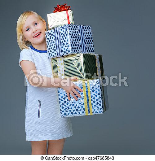 happy elegant child on grey holding pile of Christmas giftes - csp47685843