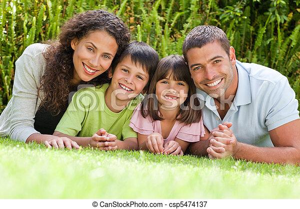 Happy family lying down in the garden - csp5474137