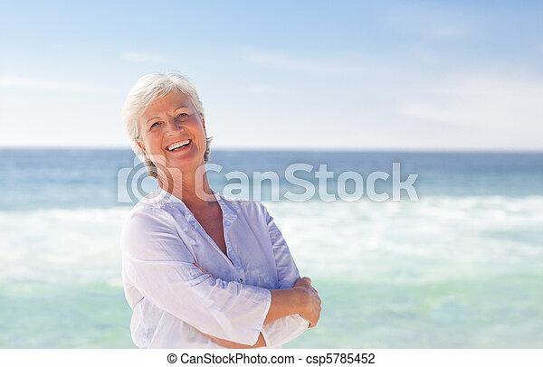 Happy retired woman on the beach - csp5785452
