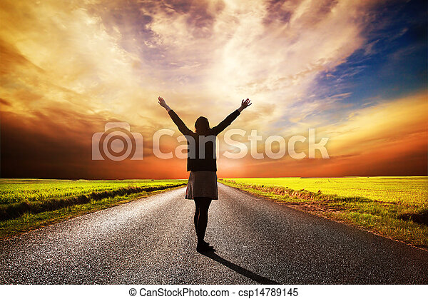 Happy woman standing on long road at sunset - csp14789145