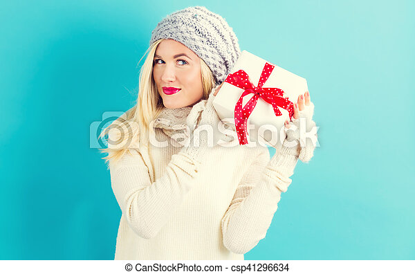 Happy young woman holding a Christmas gift - csp41296634