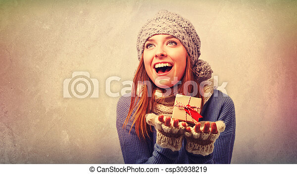 Happy young woman holding a gift box - csp30938219