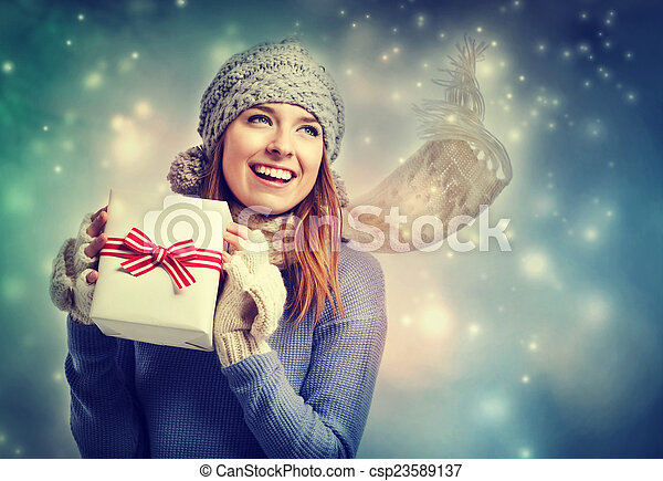 Happy young woman holding a present box - csp23589137
