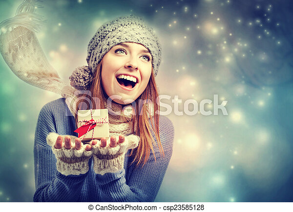 Happy young woman holding a small present box - csp23585128