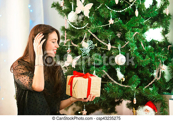 Happy young woman holding christmas present box on Christmas eve - csp43235275