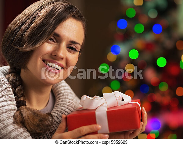 Happy young woman holding christmas present box in front of christmas lights - csp15352623
