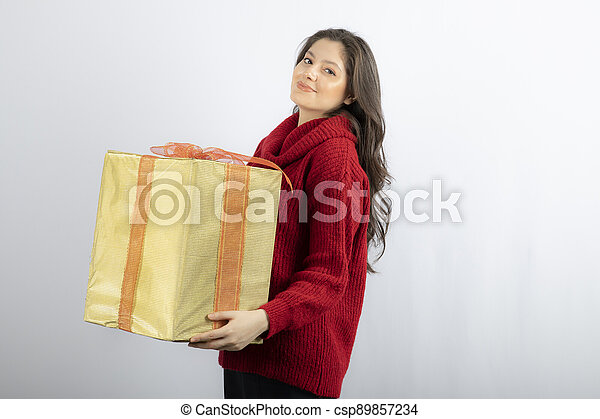 Happy young woman holding Christmas present box - csp89857234