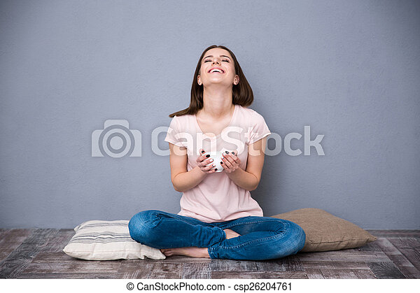 Happy young woman sitting on the floor with cup of coffee - csp26204761