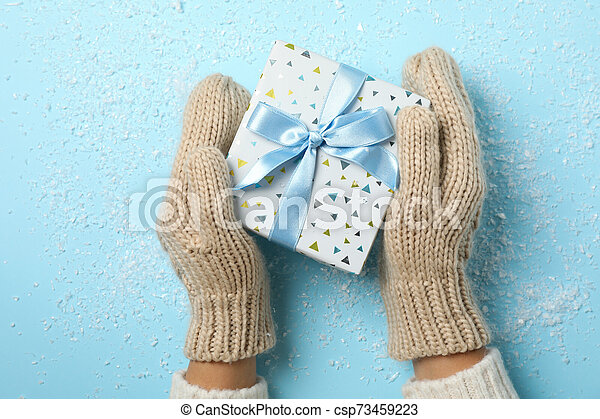 holding in hands present on blue background with snow, space for text - csp73459223