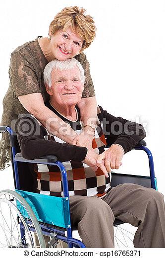 loving senior wife hugging disabled husband - csp16765371