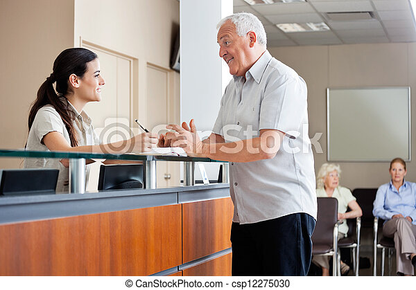 Man Communicating With Female Receptionist - csp12275030