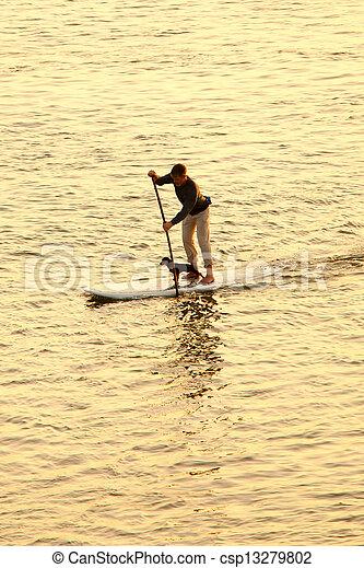 man paddleboarding with dog - csp13279802