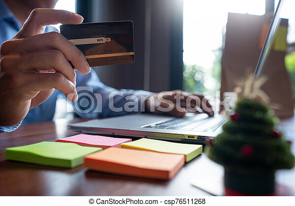 Man paying with credit card and entering security code for online shopping making a payment or purchasing goods on the internet with laptop computer, online shopping concept - csp76511268