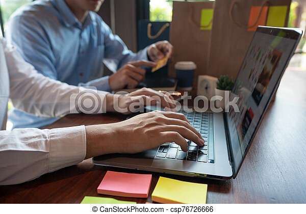 Man paying with credit card and entering security code for online shopping making a payment or purchasing goods on the internet with laptop computer, online shopping concept - csp76726666
