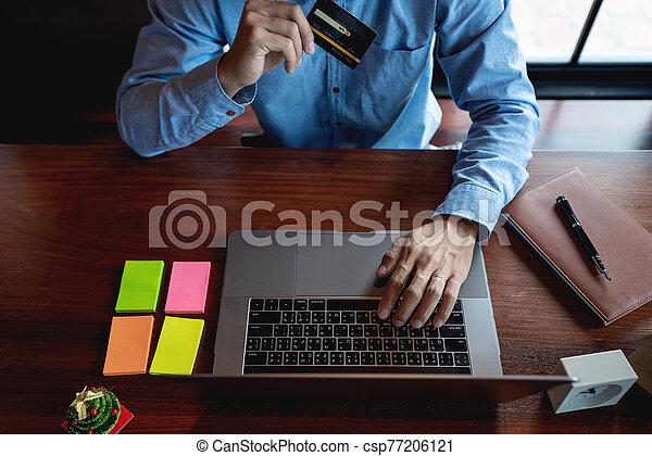 Man paying with credit card and entering security code for online shopping making a payment or purchasing goods on the internet with laptop computer, online shopping concept - csp77206121