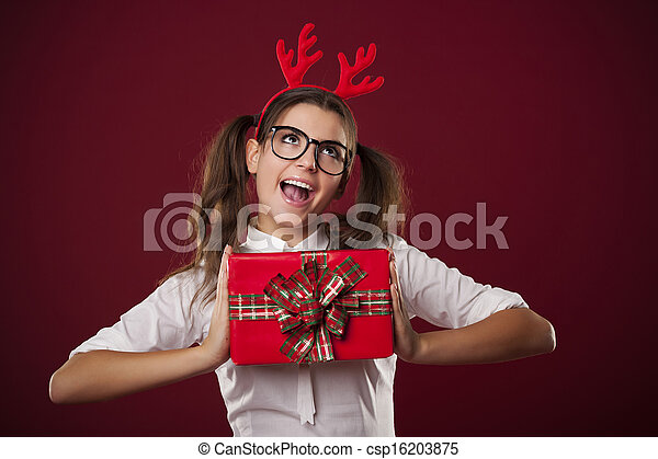 Nerdy woman holding red christmas present - csp16203875