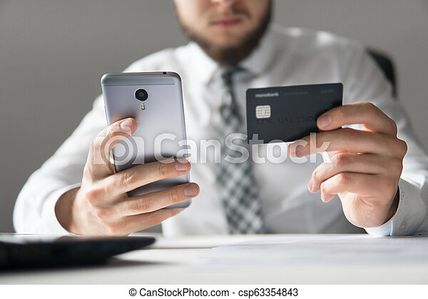 Online trading on the currency exchange. Smartphone and Internet Commerce. Payment of goods online. Online payments through the phone. Young businessman with a bank credit card in his hands. - csp63354843