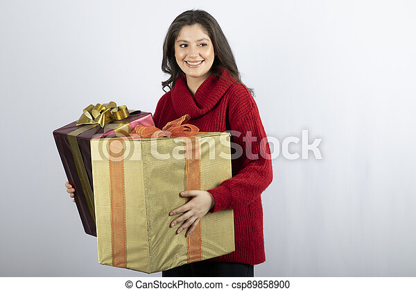 Pretty woman in red sweater holding Christmas presents - csp89858900