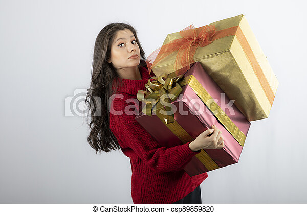 Pretty woman in red sweater holding two boxes of Christmas presents - csp89859820