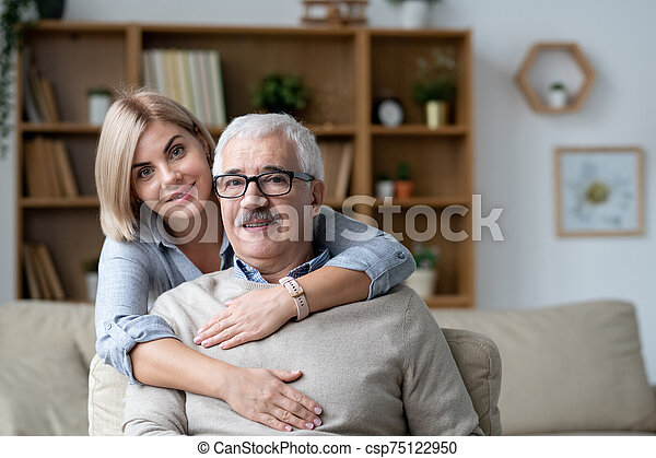 Pretty young woman embracing senior father sitting on couch in front of camera - csp75122950