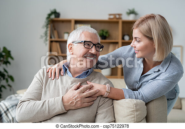 Restful senior man on couch looking at his young daughter standing near by - csp75122978