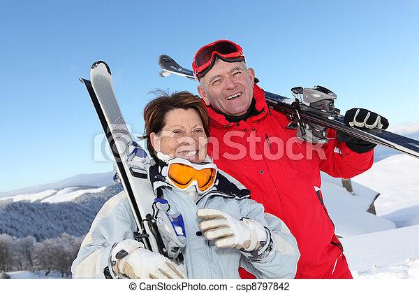 Retired couple having fun on a skiing trip - csp8797842