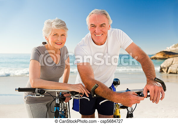 Retired couple with their bikes on the beach - csp5684727