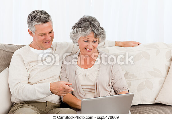 Retired lovers looking at their laptop - csp5478609