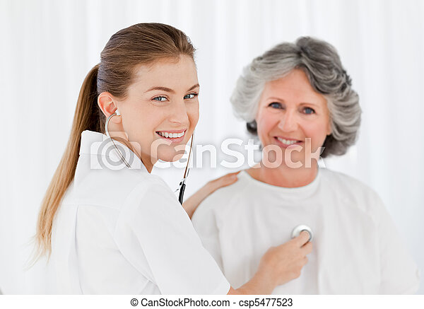Retired patient with her nurse looking at the camera - csp5477523