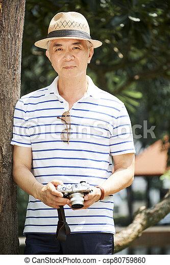 Senior Chinese man with digital camera - csp80759860