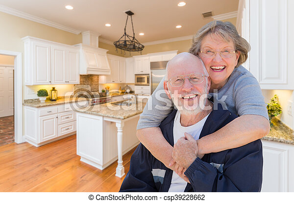 Senior Couple Hugging Inside Custom Kitchen - csp39228662