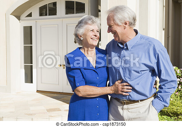 Senior couple standing outside house - csp1873150